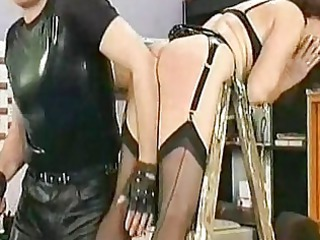 lady slave in leather bending over a ladder is